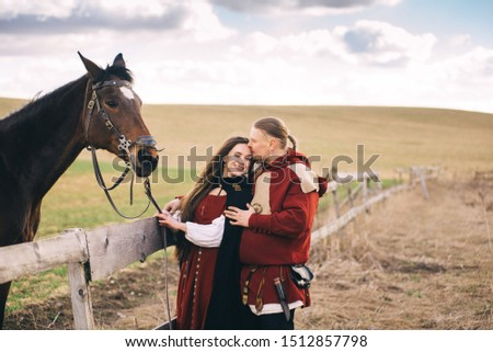 A couple in love with a horse in folk costumes in the field and near the Church #1512857798