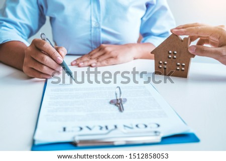 Sale Agent giving house keys to woman customer and sign agreement documents for realty purchase. #1512858053