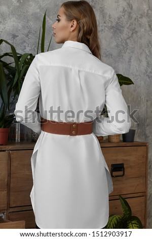 Medium full back shot of a young European lady dressed in a white long-sleeved tunic shirt and a wide brown elastic band with leather facing and two bronze press studs.  #1512903917
