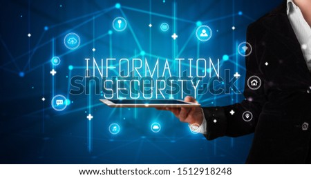 Young business person working on tablet and shows the digital sign: INFORMATION SECURITY #1512918248