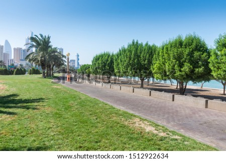 Kuwait, Kuwait City, Gulf Road - September 20, 2019 - Trees and grass with sea and buildings in the background. - image  #1512922634