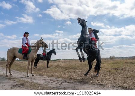 Slavuta, Ukraine - september 22, 2019 : Ukrainian men on horseback participate in the Ethno-eco festival Kolodar in city Slavuta, Ukraine #1513025414