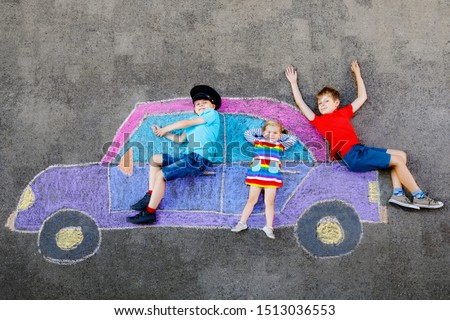 three little children, two school kids boys and toddler girl having fun with with car picture drawing with colorful chalks on asphalt. Siblings painting on ground playing together. Creative leisure