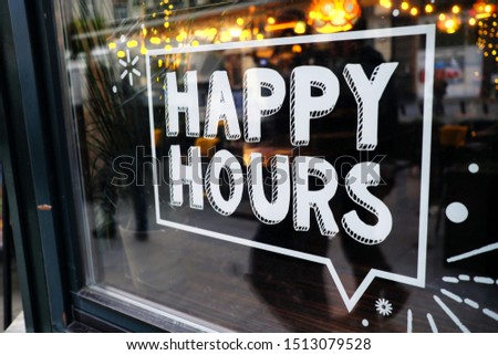 white 'happy hours' sign on restaurant window with beautiful bokeh balls in the background.
