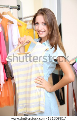 Beautiful girl chooses clothes on room background #151309817