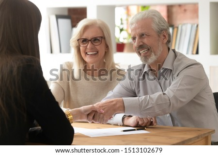 People sit at desk in office focus on aged couple handshaking with female realtor real estate agent succeed agreement, after sign contract client express gratitude shake hands, successful deal concept #1513102679