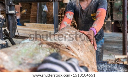 worker sawing a hardwood on saw table in Thailand #1513104551