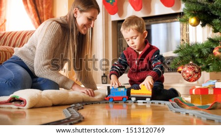 Portrait of boy with mother playing on floor with toy train and railways. Child receiving presents and toys on New Year or Xmas #1513120769