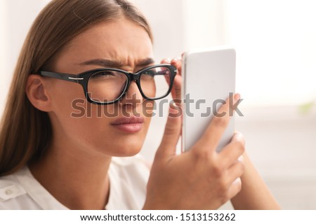 Poor Eyesight Concept. Girl Looking At Cellphone Screen Through Eyeglasses Having Vision Problem Indoor. Selective Focus Royalty-Free Stock Photo #1513153262