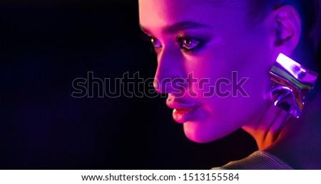 Woman wearing earrings in colorful bright neon lights, posing in studio, free space #1513155584