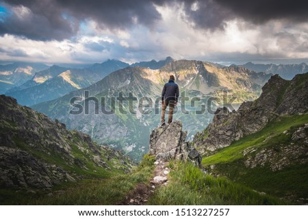 Male hiker standing on a rock above deep valley in front of scenic panorama of high mountains with dark clouds above him. #1513227257
