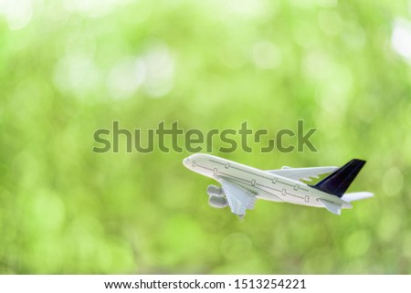 Freight forwarder, shipping courier agent service, aviation concept : White comercial plane / airplane fly over a green bokeh background, depict transporting of goods or parcel to overseas destination #1513254221