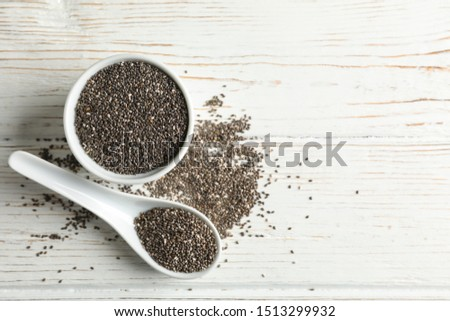 Ceramic sauce boat and spoon with chia on wooden background, top view #1513299932