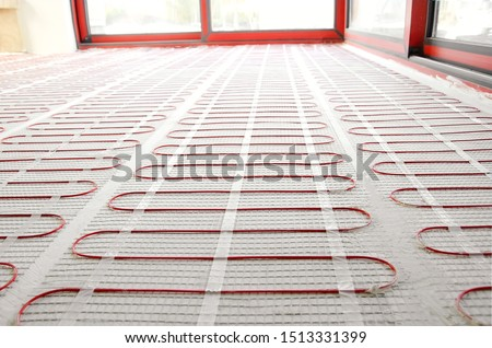 Electric underfloor heating red mats on cement floor. Heating red electrical cable on cement floor copy space background. Renovation and construction, comfortable warm home concept. Royalty-Free Stock Photo #1513331399