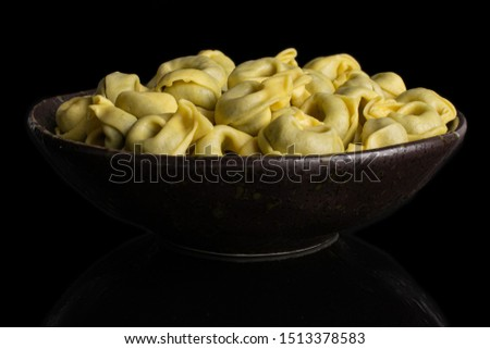 Lot of whole fresh yellow spinach filled tortelloni in dark ceramic bowl isolated on black glass #1513378583