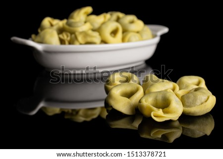 Lot of whole fresh yellow spinach filled tortelloni in white oval ceramic bowl isolated on black glass #1513378721