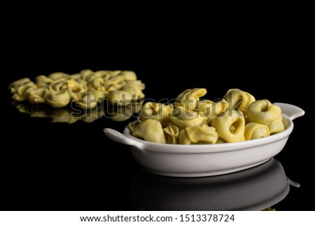 Lot of whole fresh yellow spinach filled tortelloni in white oval ceramic bowl isolated on black glass #1513378724