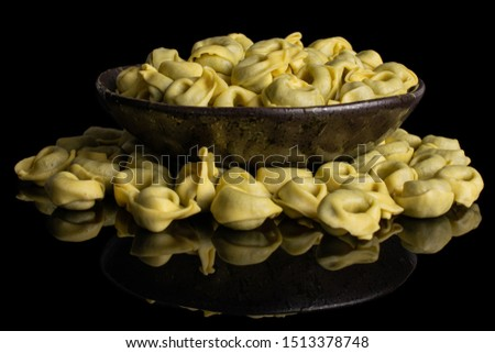 Lot of whole fresh yellow spinach filled tortelloni in dark ceramic bowl isolated on black glass #1513378748