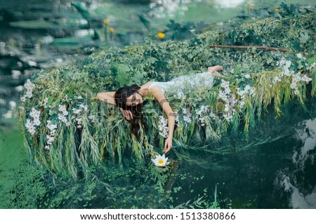 cute brunette woman long hair lies in boat  gently touches water lily her hand. princess bride dress floats on lake. Friday, sleeping relaxation enjoyment. Creative wedding decor natural cosmetics
