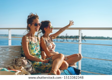 Two young women girl friends or sisters sitting on the bench on the deck of the ferry boat or ship sailing to the island tourist destination on summer vacation waving to the horizon in sunny day Royalty-Free Stock Photo #1513382348