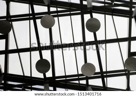 Reworked photo of transparent ceiling with metal framework and round lighting fixtures in an office building. Abstract black and white modern architecture background with geometric structure. #1513401716