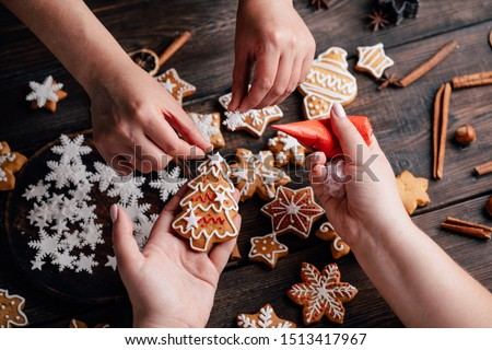 Christmas bakery. Friends decorating freshly baked gingerbread cookies with icing and confectionery mastic. Festive food, family culinary, Christmas and New Year traditions concept #1513417967