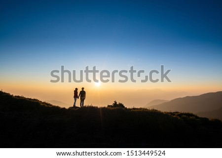 Silhoutte of a couple hold hand of each other looking at sunset on top of hill with background of mountain and golden color of sunshine. Concept of teamwork, successful. #1513449524