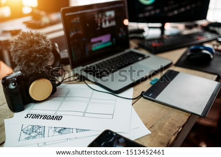 Close up storyboard content planning of production media of the Blogger or Vlog and the laptop and camera on the desk work