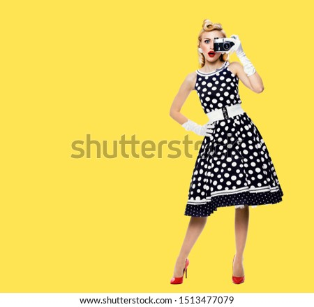 Full body portrait of young woman with noname old film camera, taking picture, dressed in pin up style black dress in white polka dot. Blond girl posing in retro fashion and vintage concept picture.
