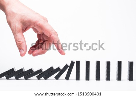 Hand pushing dominoes. Domino effect. Structural instability #1513500401