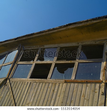 Broken windows of a houseseemingly abandoned, angled low angle shot #1513514054