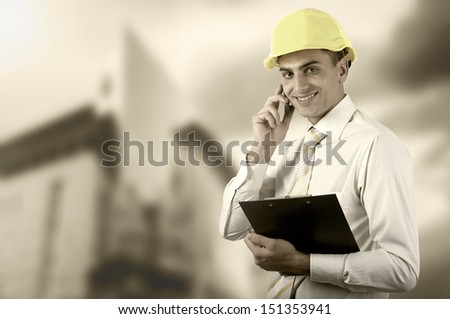 Young architect wearing a protective helmet standing on the building outdoor background #151353941