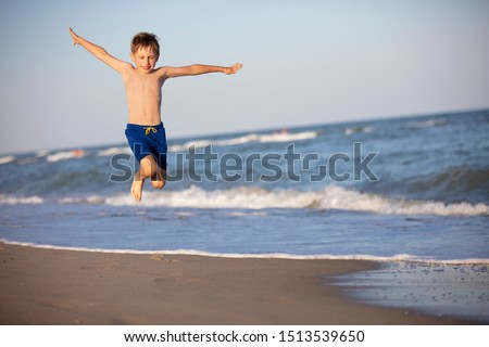 A child plays on the beach. A happy boy jumps high by the sea. Active holiday on the beach #1513539650