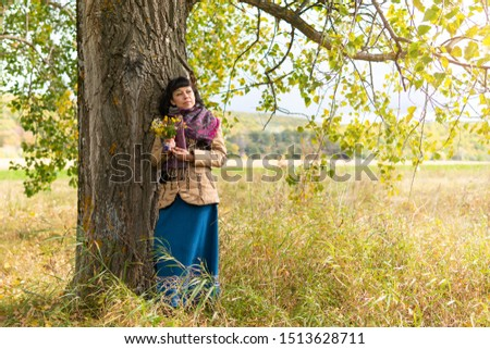 Beautiful woman standing under a tree in a Park in nature. She holds flowers in her hands. Autumn. #1513628711