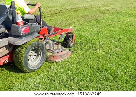 A man rides a lawn mower. Lawn Care. Riding Mower. Grass #1513662245