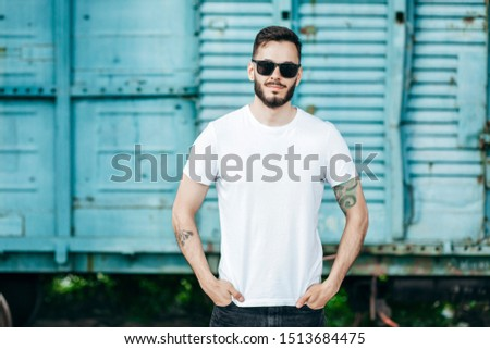 A young stylish man with a beard in a white T-shirt and glasses. Street photo #1513684475