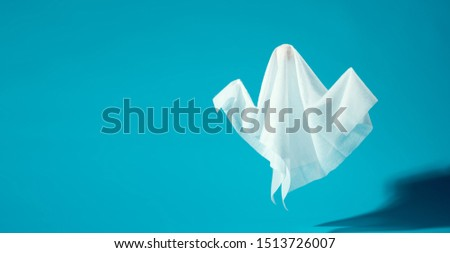 Image of halloween ghosts made of white fabric on empty blue background