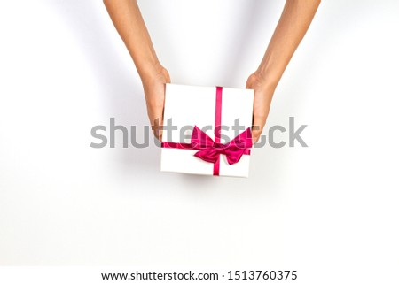 Child hands holding present gift box tied with ribbon on white background. Top view, place for text. Holiday concept #1513760375