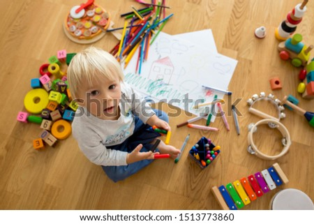 Little blonde toddler boy, drawing with pastels and coloring pens, playing with early development wooden toys #1513773860