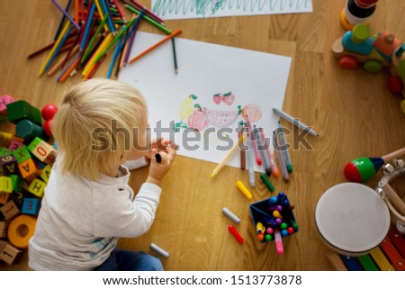 Little blonde toddler boy, drawing with pastels and coloring pens, playing with early development wooden toys #1513773878