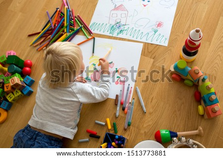 Little blonde toddler boy, drawing with pastels and coloring pens, playing with early development wooden toys #1513773881