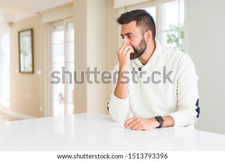 Handsome hispanic man wearing casual white sweater at home looking stressed and nervous with hands on mouth biting nails. Anxiety problem. #1513793396