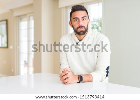 Handsome hispanic man wearing casual white sweater at home puffing cheeks with funny face. Mouth inflated with air, crazy expression. #1513793414