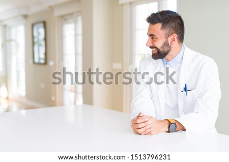 Handsome hispanic doctor or therapist man wearing medical coat at the clinic looking away to side with smile on face, natural expression. Laughing confident. #1513796231