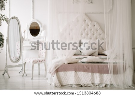 White bedroom interior with nobody. large cozy bed with a white canopy and oval dressing mirror with dressing table next to it