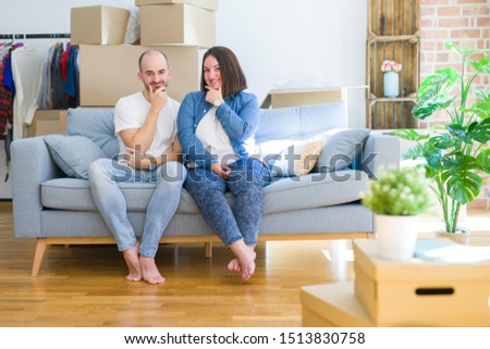 Young couple sitting on the sofa arround cardboard boxes moving to a new house looking confident at the camera with smile with crossed arms and hand raised on chin. Thinking positive. #1513830758