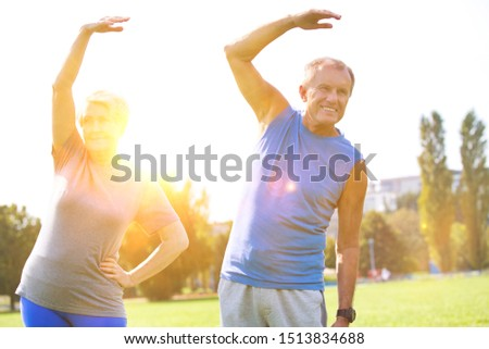 Active senior couple stretching in park with yellow lens flare in background #1513834688