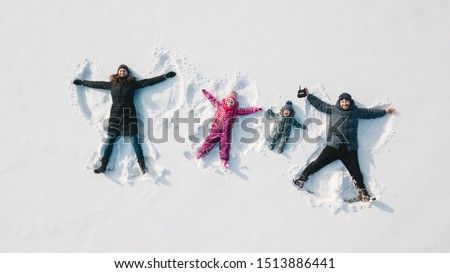 Family making a snow angel. Aerial view. Mother and father and chilren making a snow angel #1513886441