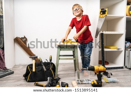 A little boy is planing an old stool with a planer. #1513895141