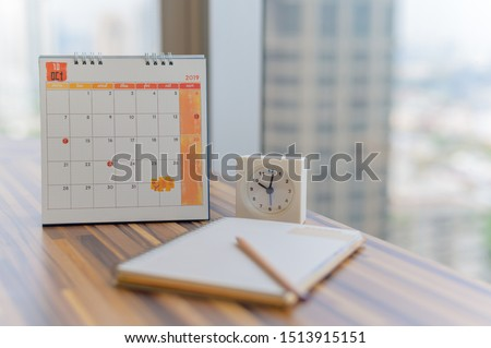 Notebook with pencil diary clock on table with October 2019 calendar at office work place with blurred background. Planning scheduling agenda Event organizer writing detail. Calendar concept. #1513915151